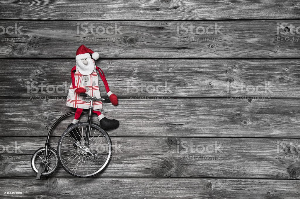 Funny red santa claus on wooden grey background. stock photo