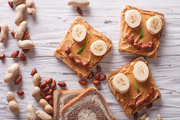 funny sandwiches with peanut butter. horizontal top view - peanutbutter bildbanksfoton och bilder