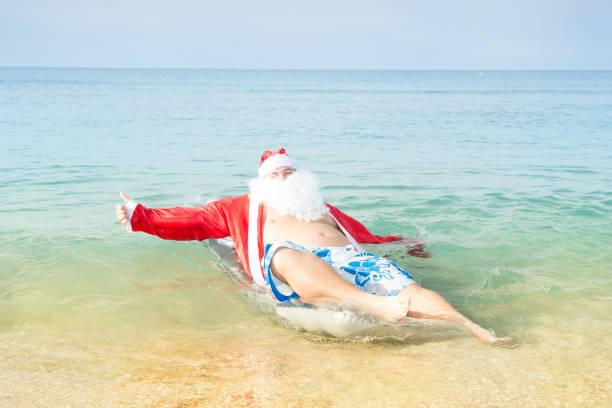 funny santa claus in the sea. - naked santa claus stock pictures, royalty-free photos & images