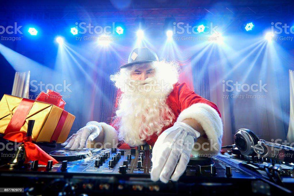 Funny Santa DJ mixes in the beams of light music. stock photo