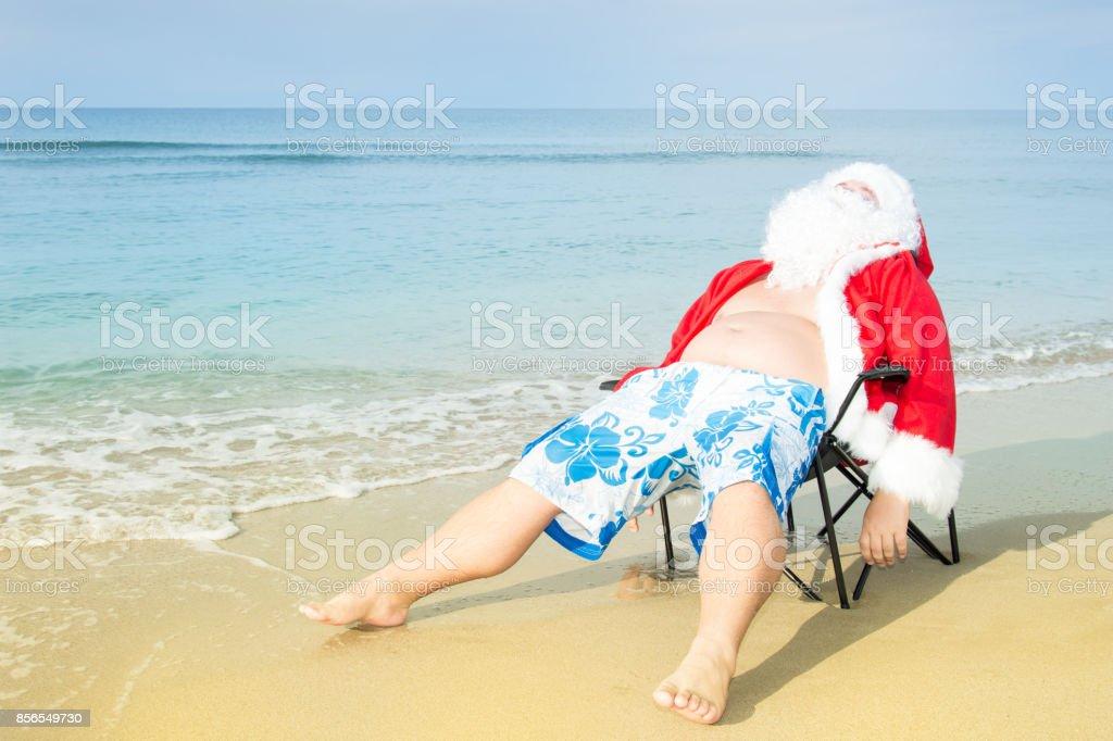 Funny Santa in shorts on the beach. stock photo