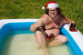 Funny naked santa. Summer, sun, rest. The man in the red hat.
