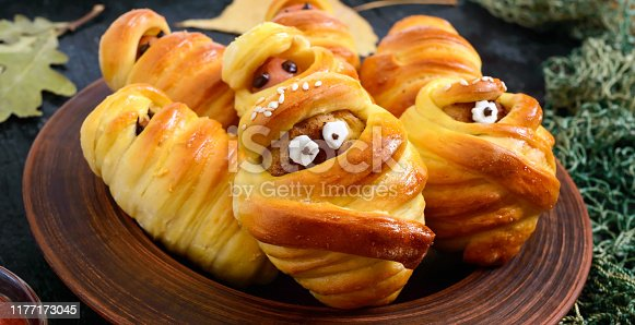istock Funny sausage and cutlets mummies in dough with eyes, ketchup on table. Halloween food. 1177173045
