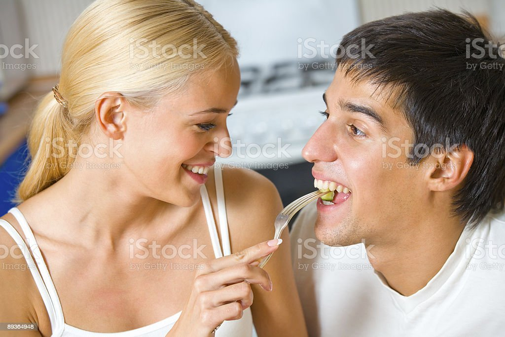Funny scene of young happy couple playfully eating at kitchen royalty-free stock photo