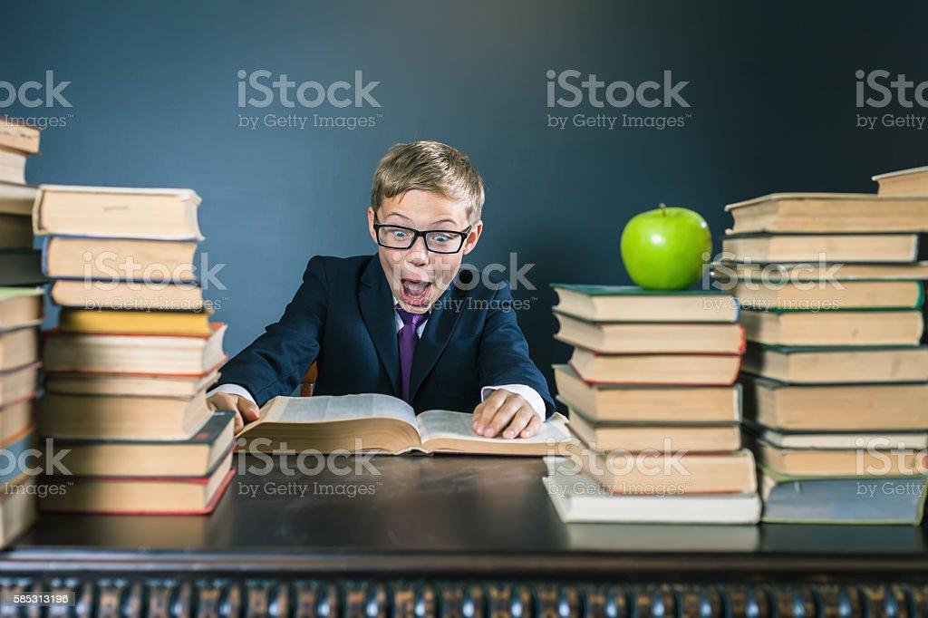 Funny school boy reading a book at library. Joke! stock photo