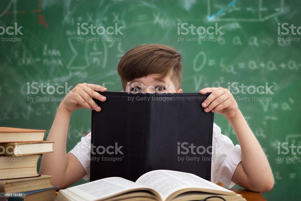 Funny schoolboy hiding behind book royalty-free stock photo
