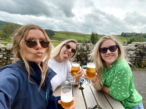 Selfie of three mid-adult friends sitting on a bench outside of a pub holding their beers in the countryside in North Yorkshire.
