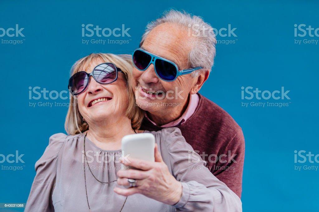 Funny senior couple taking a selfie stock photo