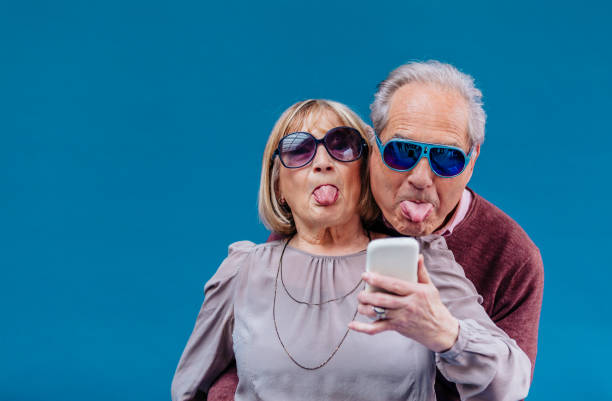 Funny senior couple taking a selfie Cheerful senior French couple making faces with color party eyeglasses and out tongues having fun while taking a selfie or making video conference chat with smart phone against blue background young at heart stock pictures, royalty-free photos & images