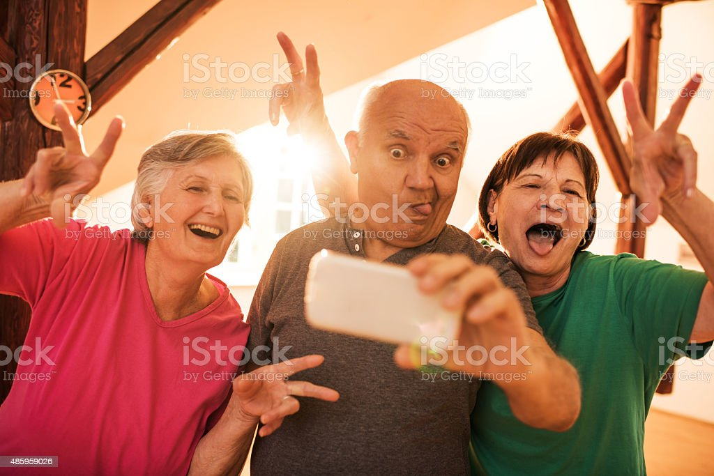 Funny senior friends taking a selfie with mobile phone. stock photo
