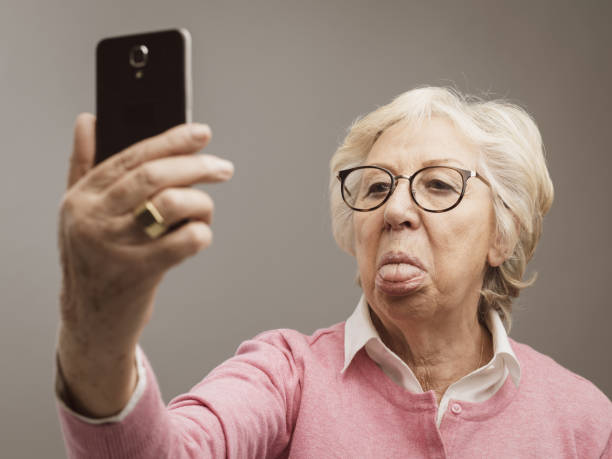 Funny senior lady taking selfies with toungue out Funny senior lady taking selfies with tongue out using her smartphone protruding stock pictures, royalty-free photos & images
