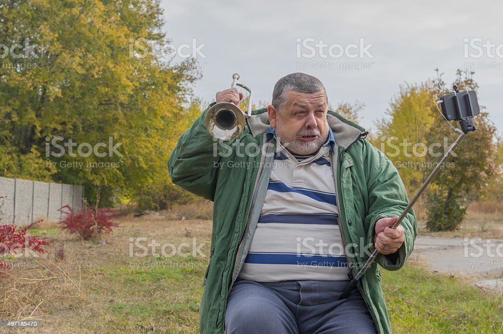 Funny senior man making faces while doing selfie outdoor stock photo
