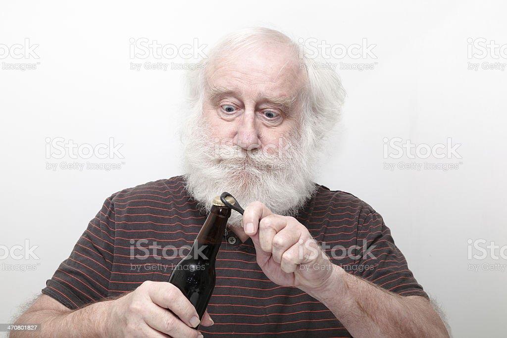 funny senior opens bottle of  dark beer stock photo