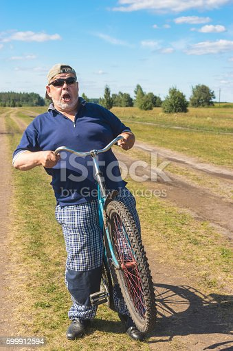 Funny senior shows his readiness to ride on a bicycle at country road
