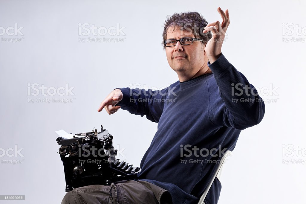 Funny shot of man with old typewriter in his lap royalty-free stock photo