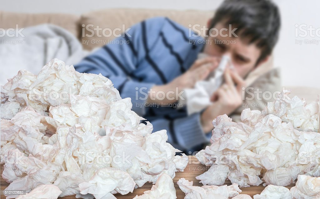 Funny sick man who has flu blowing nose with tissues stock photo