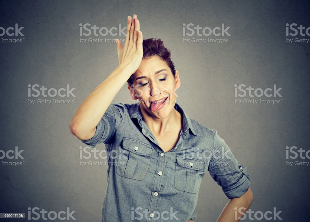 Funny silly young woman, slapping hand on head having duh moment stock photo