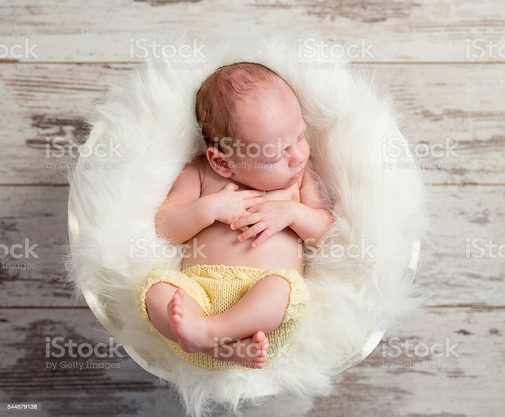 d7f81d4e1 Funny Sleepy Baby In Round Cot With Legs Up Stock Photo   More ...