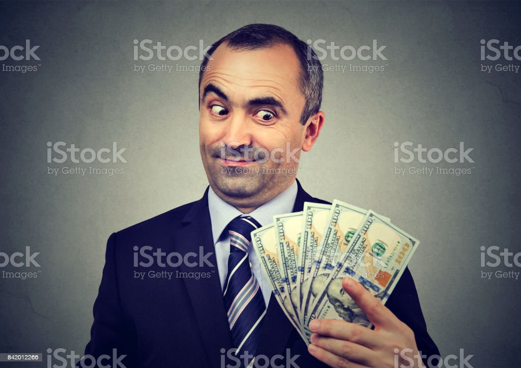 Funny sly business man holding looking at money stock photo