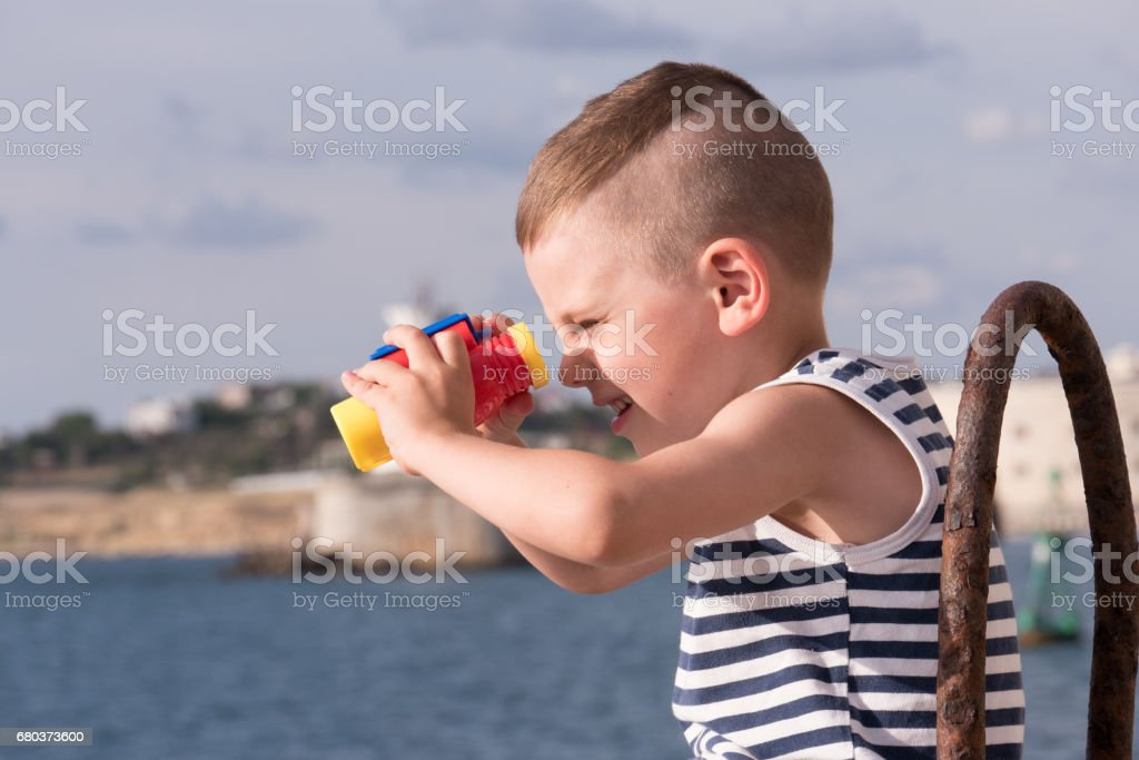 funny small boy looking into the distance through binoculars stock photo