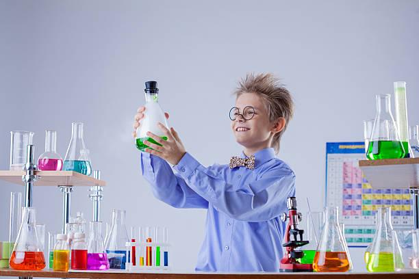 Lustige lächelnde junge holding Glaskolben mit Reagensen – Foto