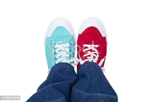 jeans and wearing different sneakers on legs
