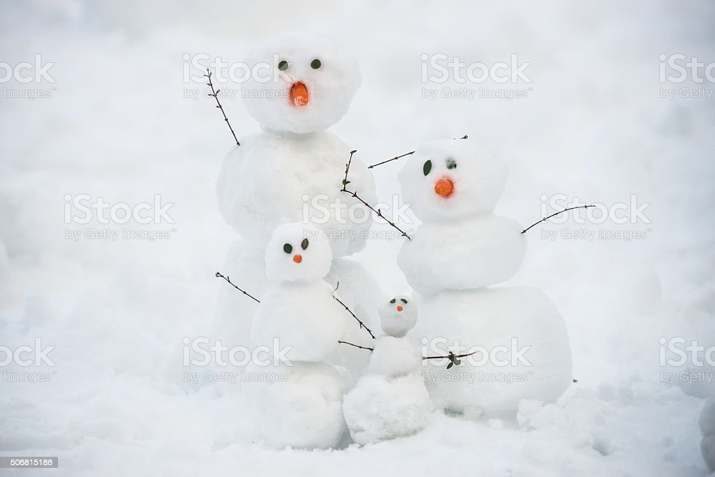 Funny snowman family on the snow stock photo
