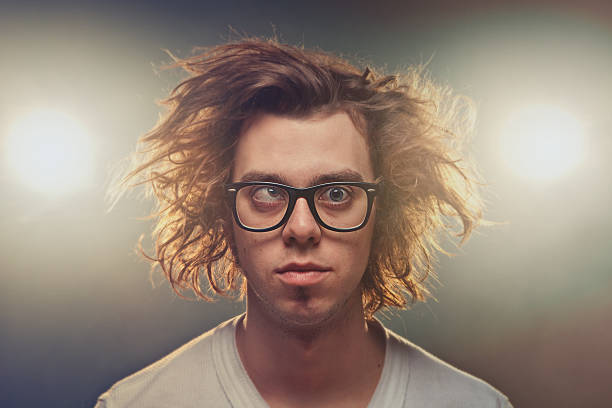 funny squinting man with tousled brown hair in studio - messy hair stock photos and pictures