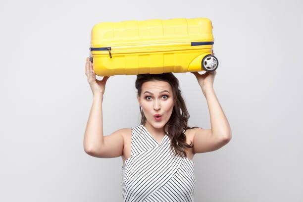 femme drôle fort jeune voyageur à rayures robe permanent et maintenant au dessus de la tête valise jaune avec visage shoked et prêt pour le voyage. - valise humour photos et images de collection