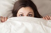 istock Funny surprised girl covering face with white blanket, headshot closeup 831554278