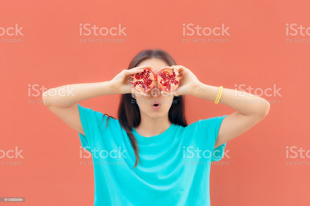 Funny Surprised Woman Holding Pomegranate Halves stock photo