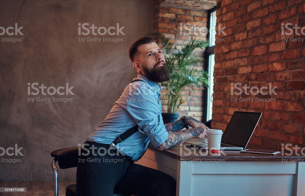 Drôle hipster tatoué dans une chemise et bretelles assis au bureau, travaillant sur un ordinateur portable, tient le café à emporter dans un bureau avec un intérieur loft. - Photo