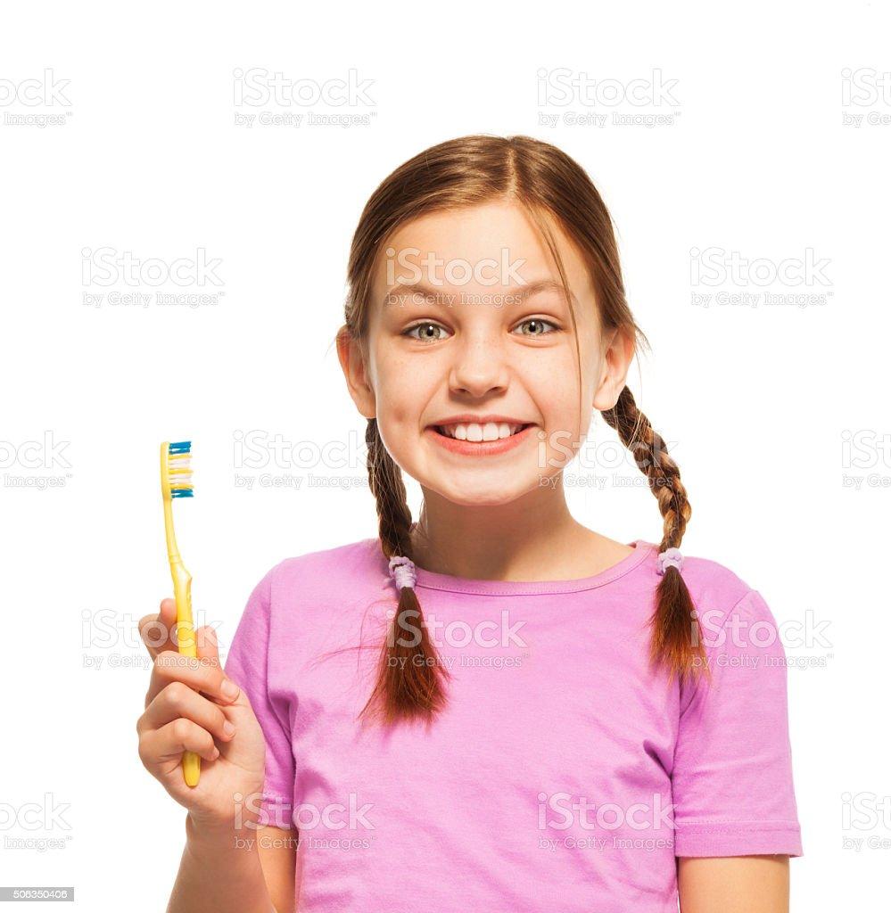 Funny teenage girl in pink tee brushing her teeth stock photo