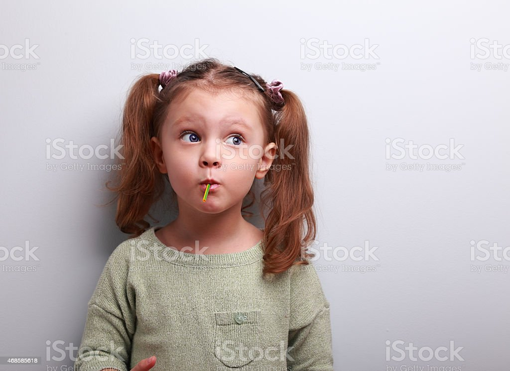 Funny thinking kid girl eating lollipop and looking up stock photo