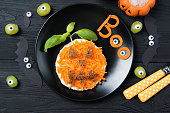 istock Funny toast with carrots in a shape of pumpkin and grapes monsters, sandwich for kids Halloween idea, top view on wooden background 835178452