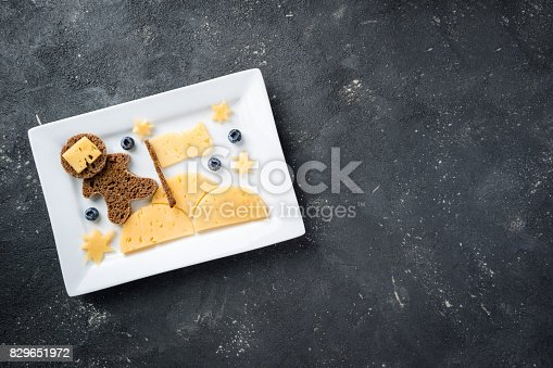 istock Funny toast with cheese and berries for kids breakfast or lunch.  Children's breakfast with creative sandwich top view 829651972