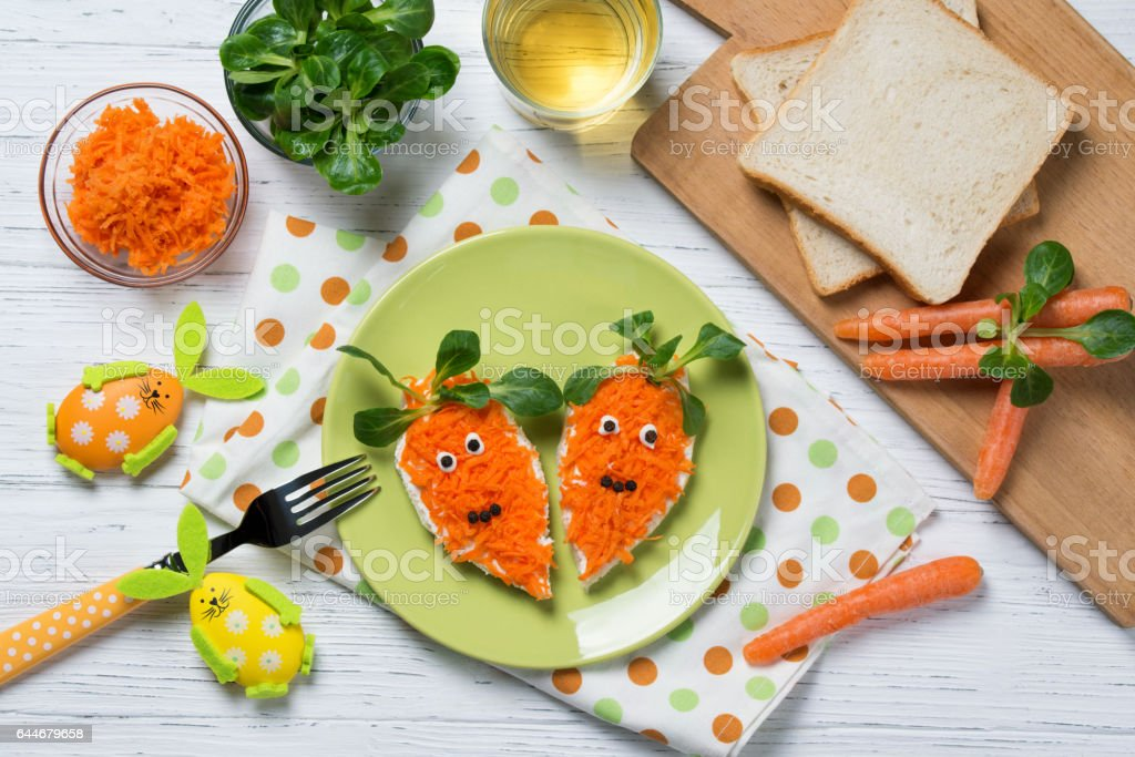 Funny toasts in a shape of carrots, food for kids Easter idea, top view stock photo