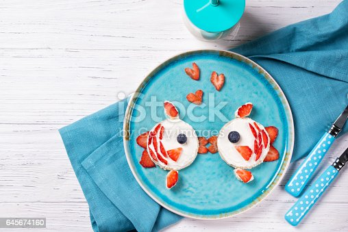 istock Funny toasts in a shape of kissing fishes, sandwich with cream cheese and berries, food for kids idea, top view 645674160