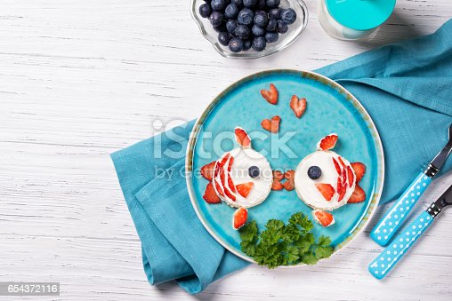 istock Funny toasts in a shape of kissing fishes, sandwich with cream cheese and berries, milk and blueberries, food for kids idea, top view 654372116