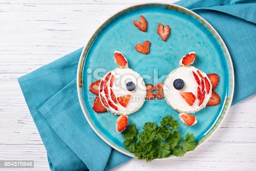 istock Funny toasts in a shape of kissing fishes, sandwich with cream cheese and berries, food for kids idea, top view 654375846