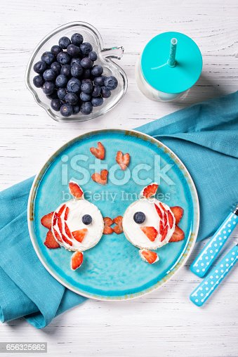 istock Funny toasts in a shape of kissing fishes, sandwich with cream cheese and berries, milk and blueberries, food for kids idea, top view 656325662