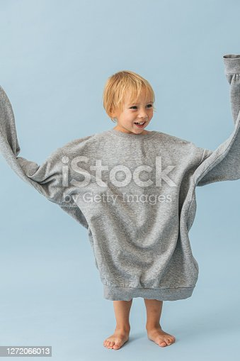 Cute smiling blond toddler boy in a huge oversized grey longsleeve spining sleeves in circle, having tons of fun. Over blue background.