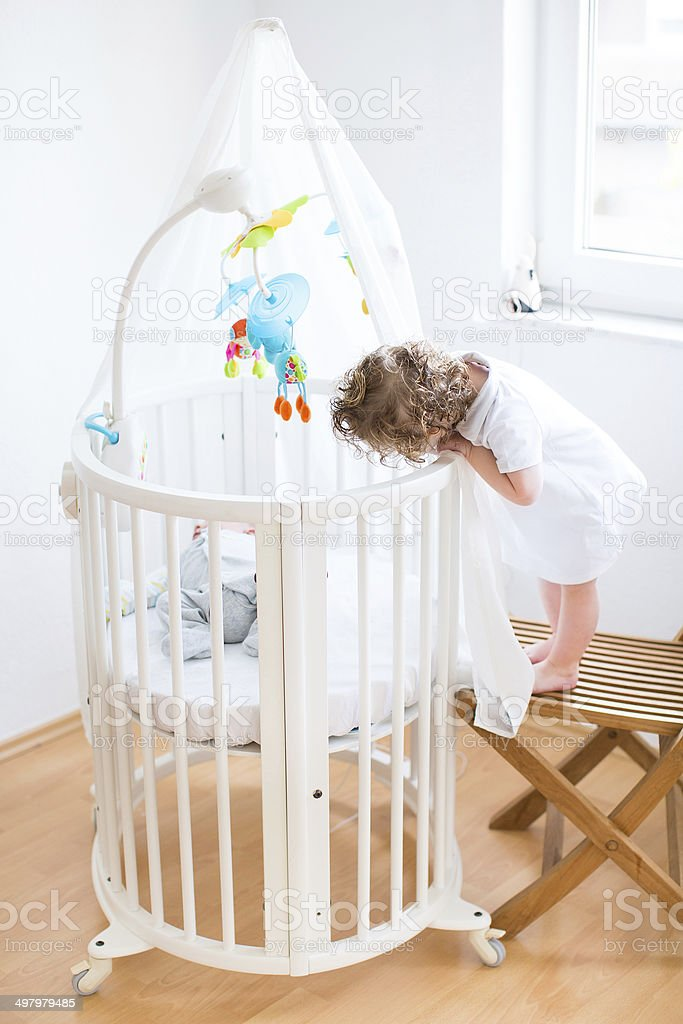 Funny toddler girl and her newborn brother in round bed royalty-free stock photo