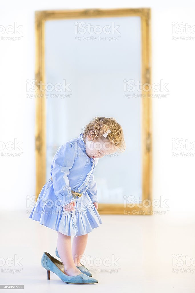 Funny toddler girl in front of big elegant mirror stock photo