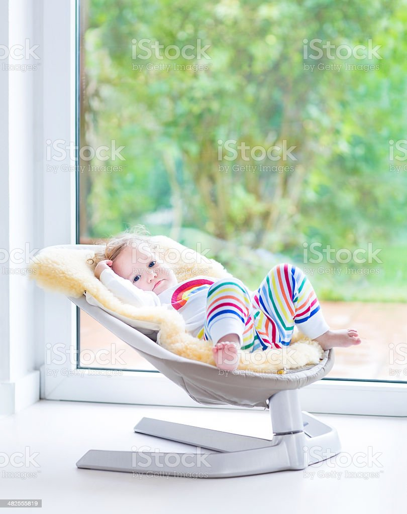Funny toddler girl in swing next to big window stock photo