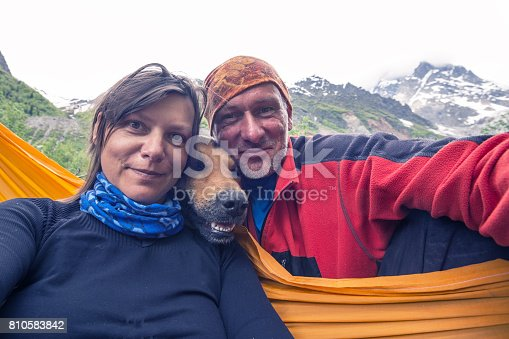 istock Funny travelers with big smiling dog, taking selfie on the mountains 810583842