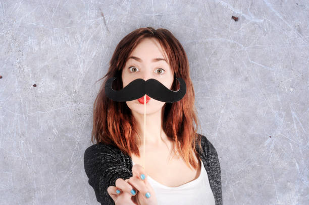 funny trendy fashion girl with paper mustache playing with emotion stock photo