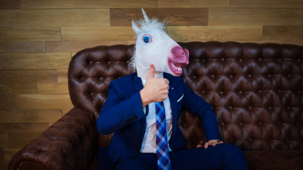 funny unicorn in elegant suit sits on sofa like a boss - unicorns stock photos and pictures