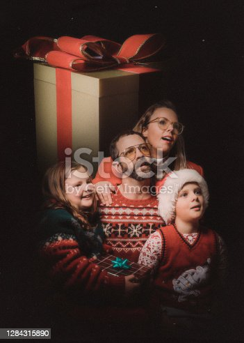 An awkward retro styled image of a family getting a studio portrait for the holiday season, wearing ugly Christmas sweaters and daydreaming of their gifts.