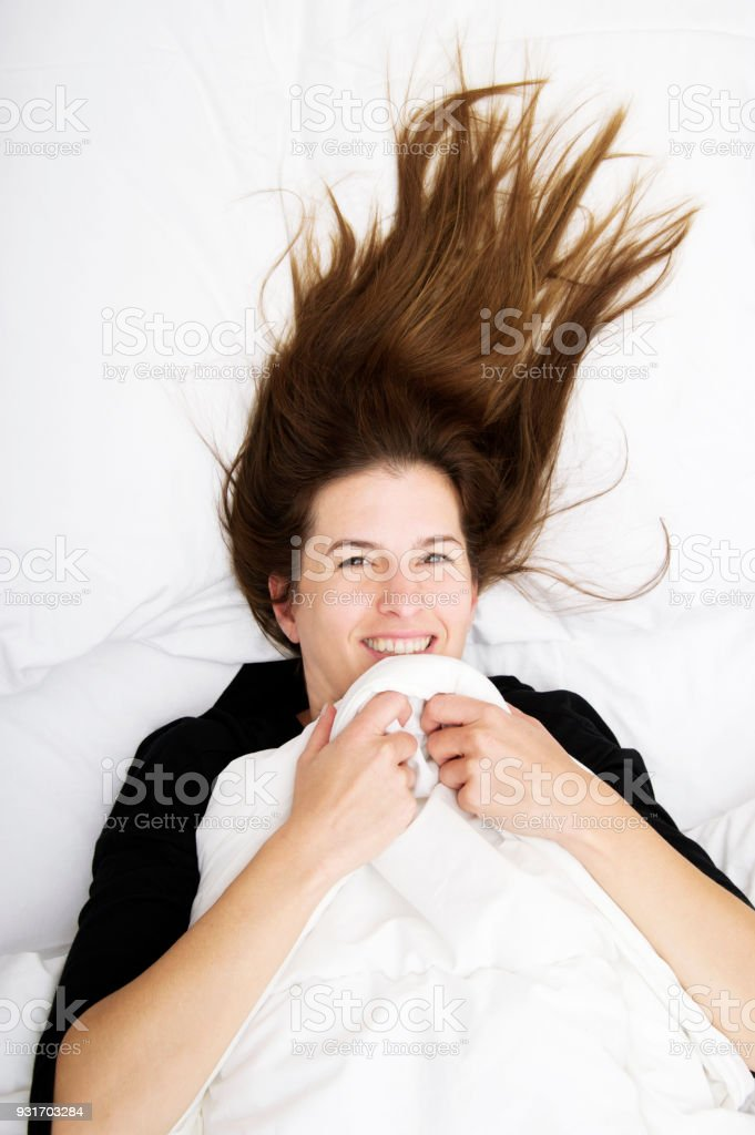 Funny wakening. Young woman is lying in her bed, smiling and joking stock photo